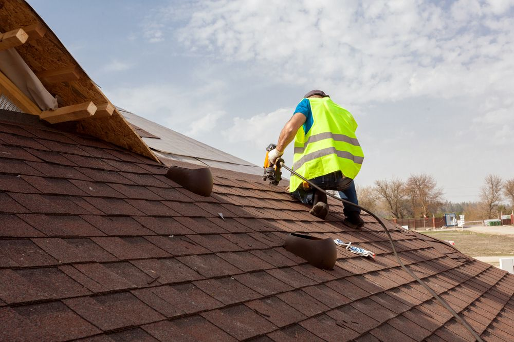 A roofer tiling a house in Surrey
